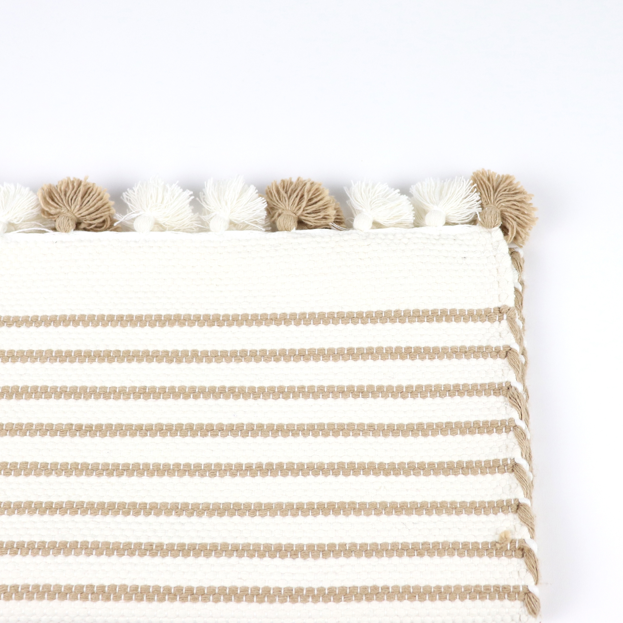 Beige and white mat with poms